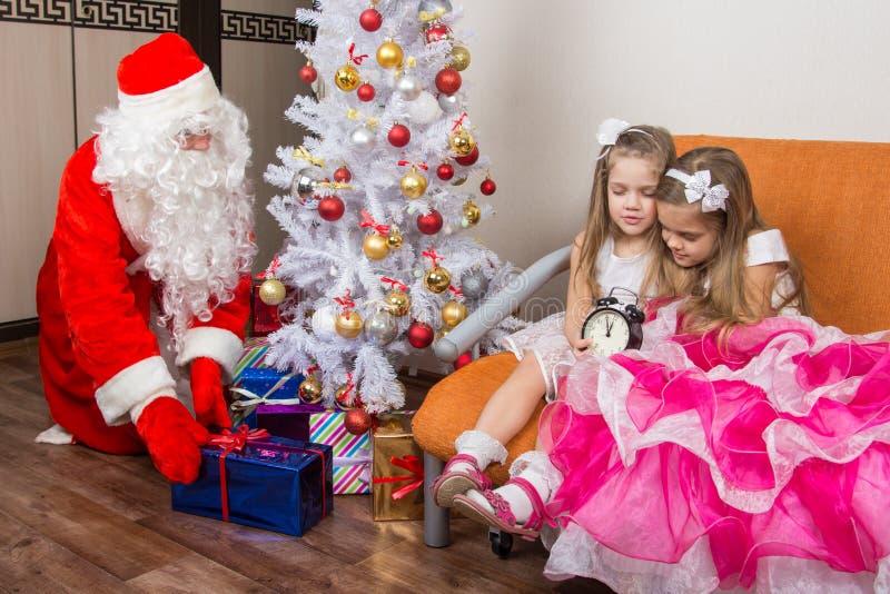 两个女孩没有等待圣诞老人并且没有去此时被投入的礼物睡,圣诞老人在圣诞树下 免版税库存图片