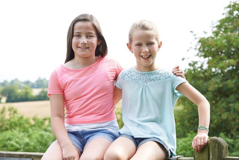 两个女孩画象一起坐门 免版税库存照片
