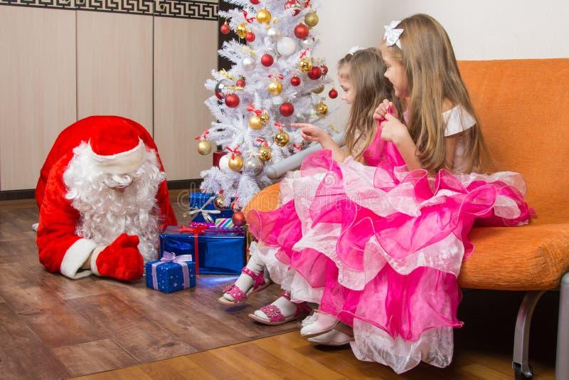 两个女孩看见圣诞老人投入礼物在圣诞树下 免版税图库摄影