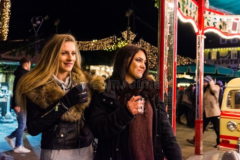 两个女孩观看快活去回合假日圣诞节市场Germa 免版税库存照片