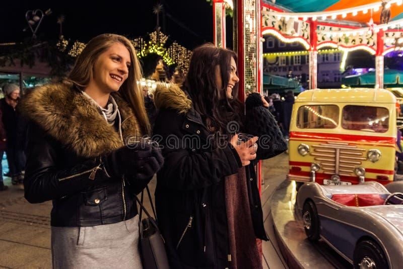 两个女孩观看快活去回合假日圣诞节市场Germa 免版税库存图片