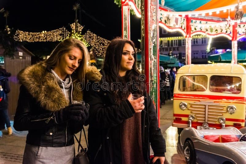 两个女孩观看快活去回合假日圣诞节市场Germa 库存照片
