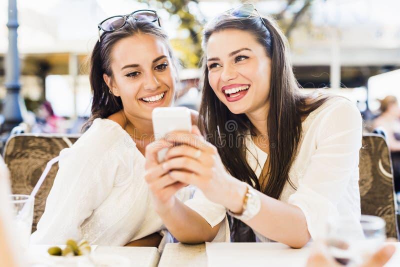 两个女孩谈话在午休期间 库存照片