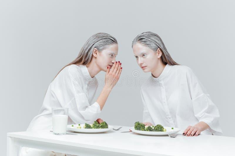 两个女孩谈话在桌上 图库摄影