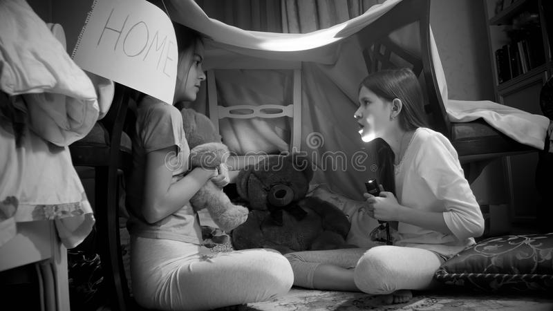 两个女孩黑白照片讲与手电的可怕故事在帐篷在卧室 库存照片