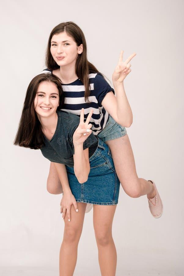 两个女孩,滑稽的面孔,鬼脸正面朋友画象  免版税库存照片
