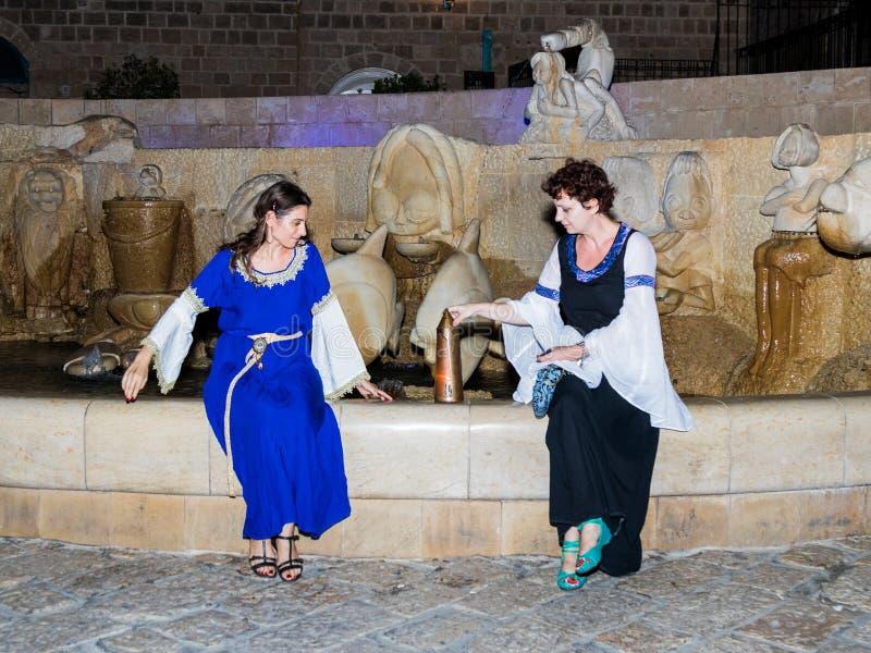 两个女孩-耶路撒冷的骑士俱乐部的成员,打扮在中世纪夫人传统服装,在晚上坐靠近 库存图片