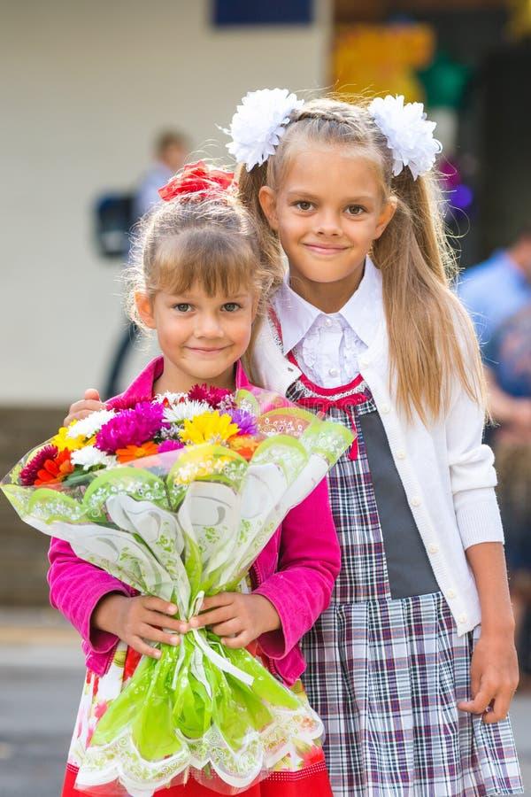 两个女孩画象在学校9月1日-一年级学生和她的妹妹有花束的在手上 免版税库存照片