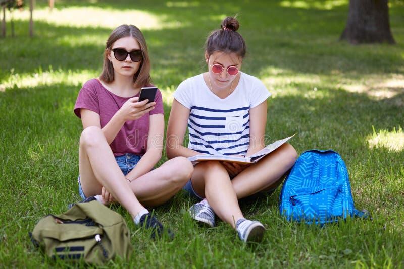 两个女性少年照片坐室外的绿草,读了书并且为冲浪社会网络使用手机,穿戴sungla 免版税图库摄影