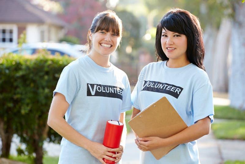 两个女性慈善志愿者画象在街道上的 图库摄影