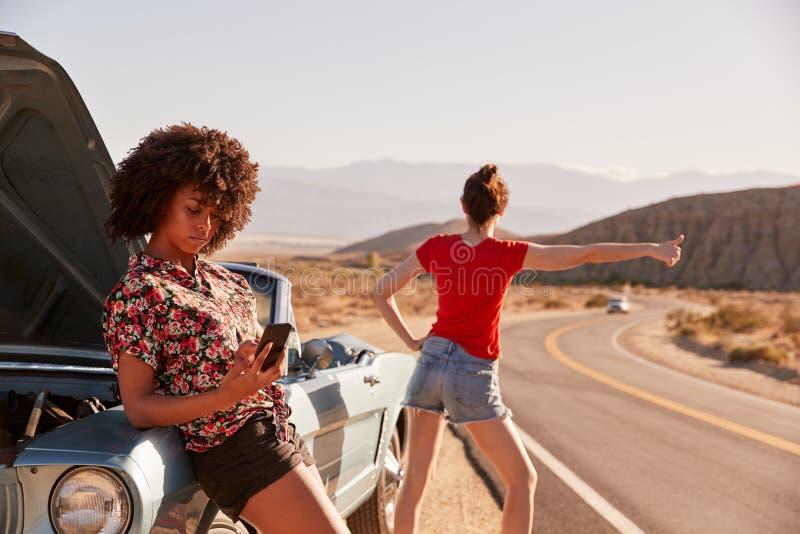 两个女性朋友乘他们在路旁的失败的汽车 免版税库存图片
