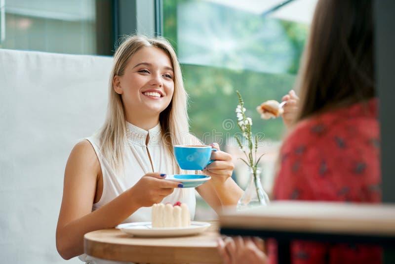 两个女性朋友有交谈在咖啡馆 图库摄影