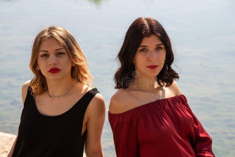 两个女性朋友特写镜头画象沿湖的岸的 免版税库存图片