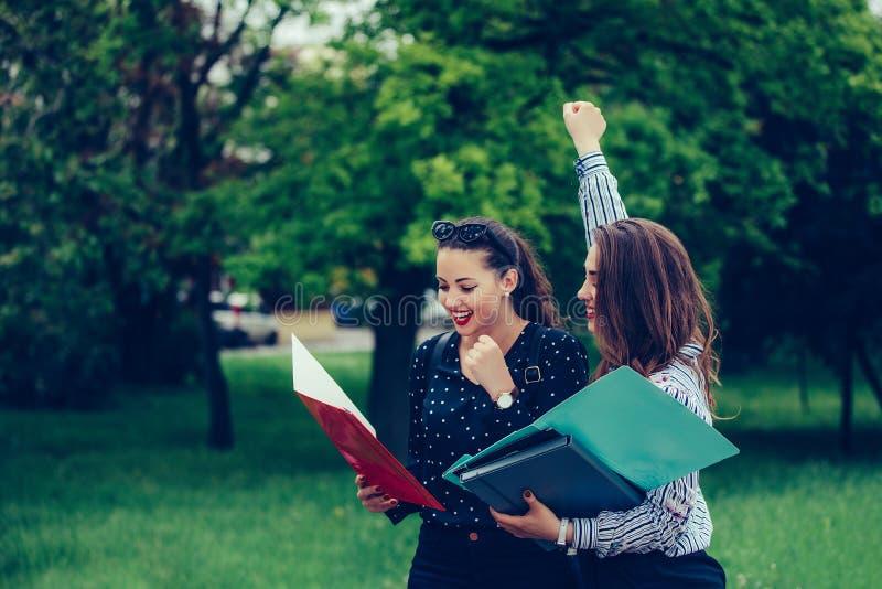 两个女性朋友,庆祝批准的检查的学生成功 图库摄影