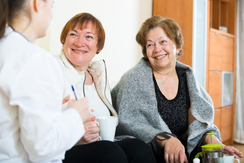 两个女性领抚恤金者谈论健康问题与医生 免版税库存图片