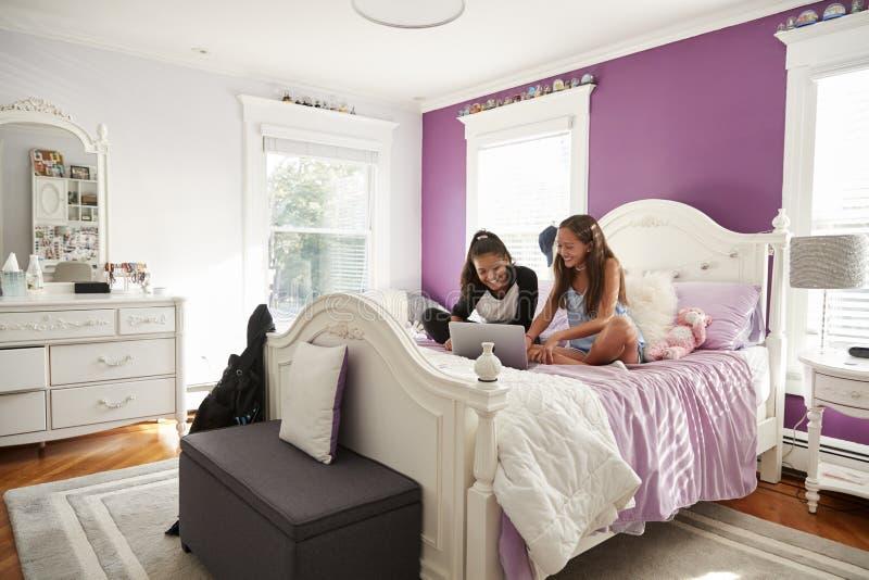 两个女朋友在卧室坐床使用膝上型计算机 免版税库存照片