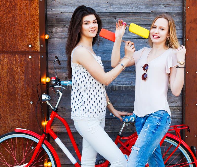 两个女朋友在时兴的成套装备,牛仔裤,上面穿戴了休息,吃冰淇凌坐一辆时髦红色葡萄酒自行车 室外 库存图片