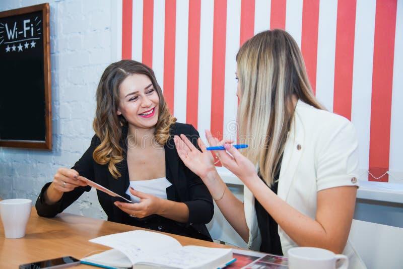 两个女朋友坐谈话一起谈论微笑 库存图片