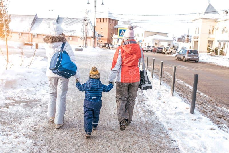 两个女朋友妈妈伴游小儿童男孩3-5年 妇女父母在沿a的城市握手,进来在冬天 免版税库存图片