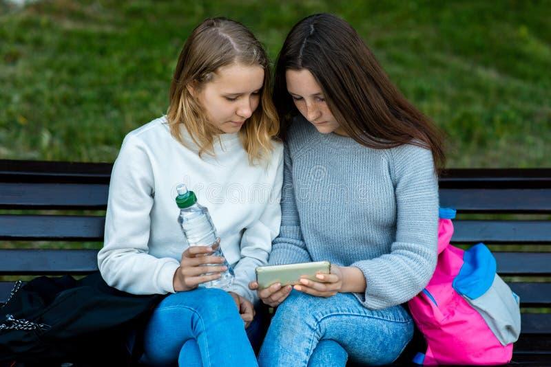 两个女朋友学生 夏天本质上 坐长凳观看在智能手机的他们一部电影 握他的手瓶 库存图片