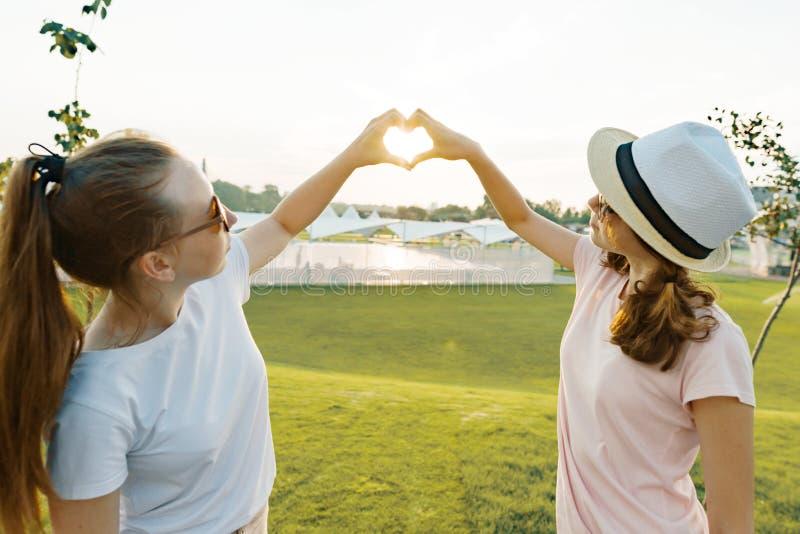 两个女朋友显示手心脏标志标志在日落在一个夏日在公园,金黄小时 图库摄影