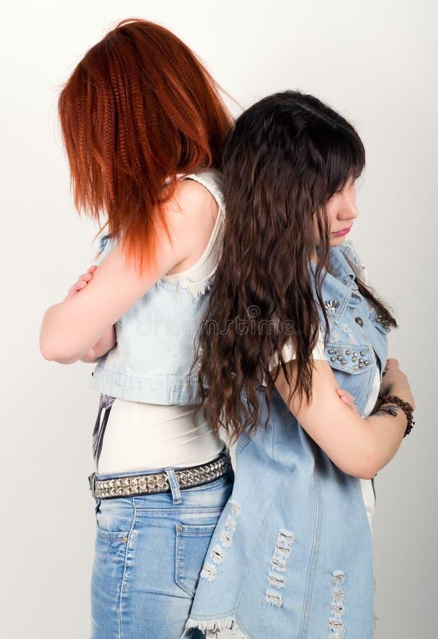 两个女朋友被触犯了,互相转动他们的后面 不同的情感 看在家在冲突以后 免版税库存照片