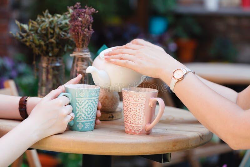 两个女朋友谈并且喝在咖啡馆的茶,户外 免版税图库摄影