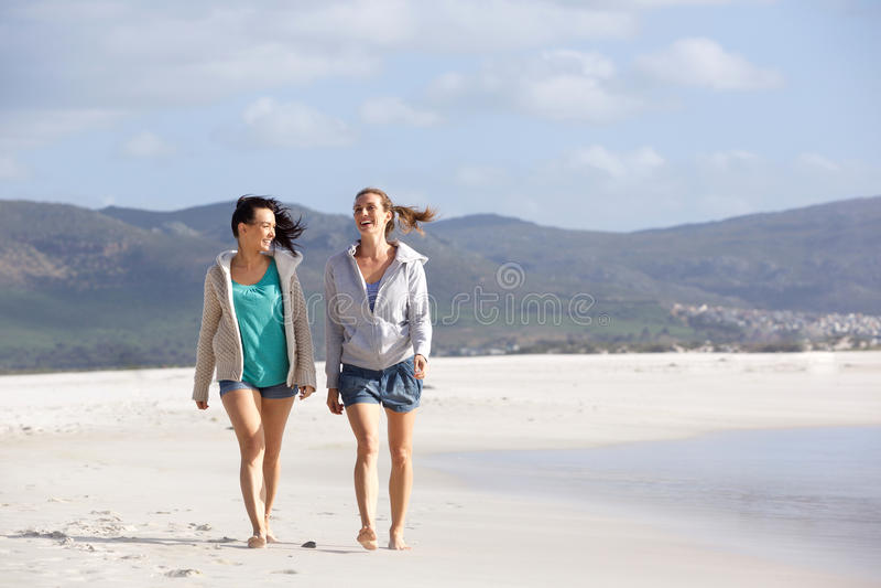 两个女朋友走和谈话在海滩 免版税库存图片
