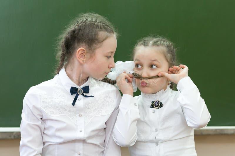 两个姐妹在学校嘲笑学校 图库摄影