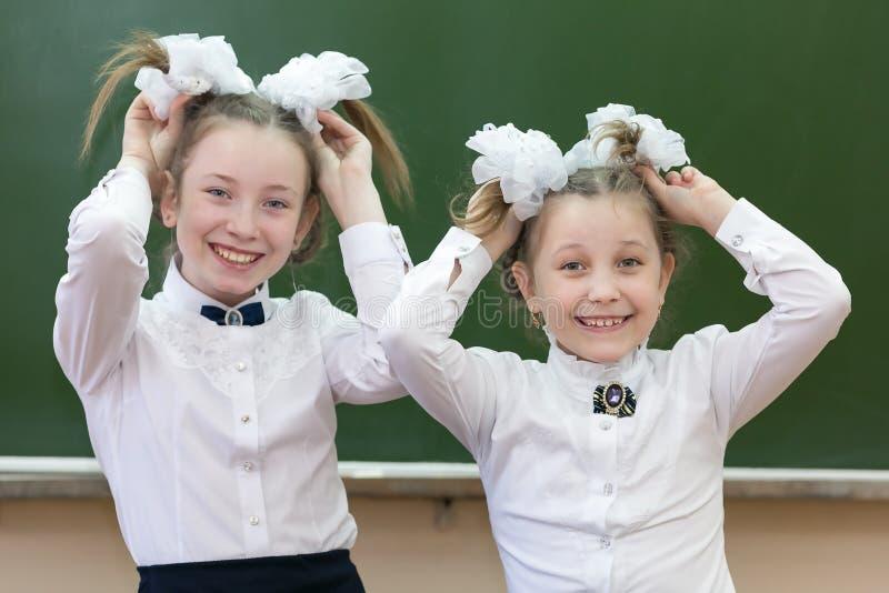 两个姐妹在学校嘲笑学校 免版税库存图片