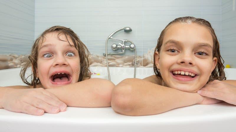 两个姐妹在浴沐浴并且做乐趣面孔 免版税库存照片
