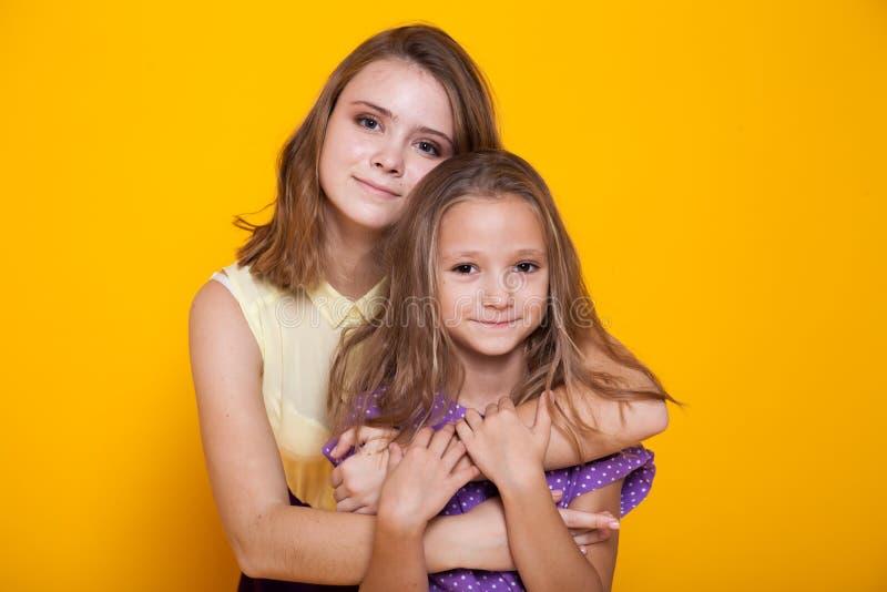 两个姐妹画象黄色背景的1 免版税库存照片