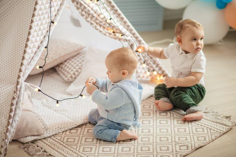 两个婴儿男孩坐在帐篷的地毯,有乐趣和在家使用与玩具 免版税库存图片