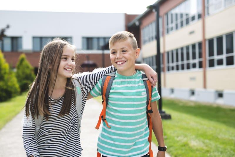 两个学校朋友画象有背包的 库存照片