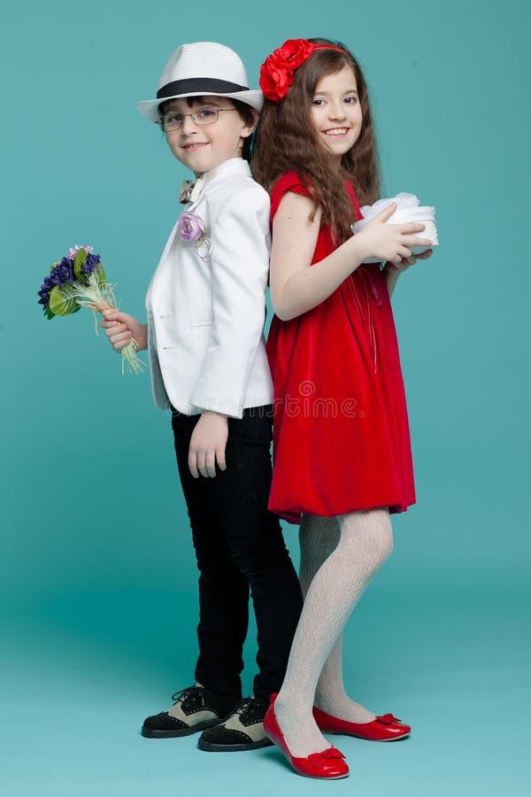 两个孩子、一个男孩衣服的,眼睛玻璃、帽子和女孩摆在演播室的红色礼服的,隔绝在绿松石背景 库存图片