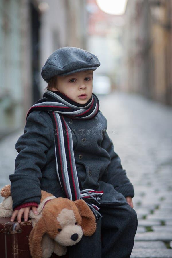 两个孩子、男孩兄弟、运载的手提箱和狗玩具,旅行在单独城市 库存图片