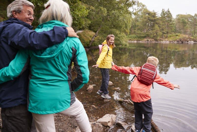 两个孩子使用在湖的岸的,他们的前景的,湖区,英国祖父母 库存图片
