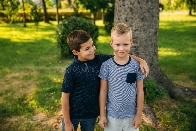 两个孩子充当公园 T恤杉和短裤的两个美丽的男孩有乐趣微笑 他们吃冰淇凌 免版税库存照片