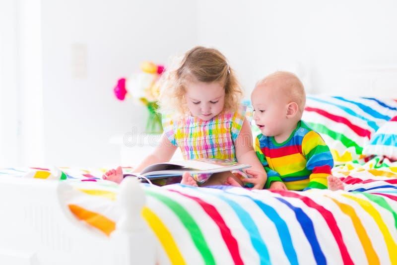 两个孩子在床上的读一本书 免版税库存照片