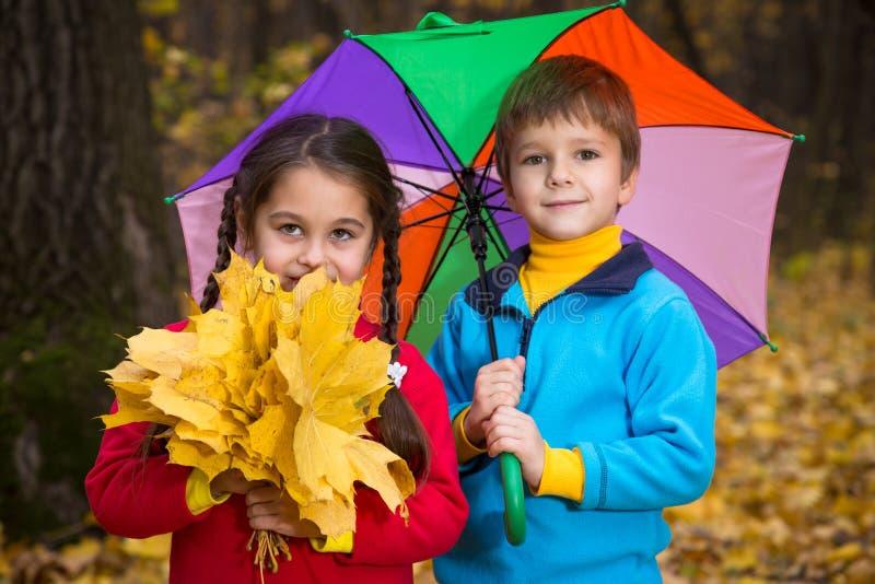 两个孩子在秋天森林里 库存图片