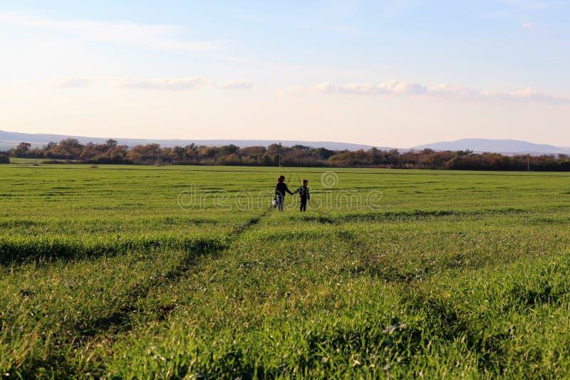 两个孩子在领域的绿色道路站立 免版税库存图片