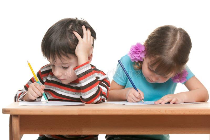 两个孩子坐在书桌并且写道 免版税库存照片