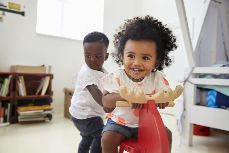 两个孩子坐在玩具的乘驾在游戏室 图库摄影