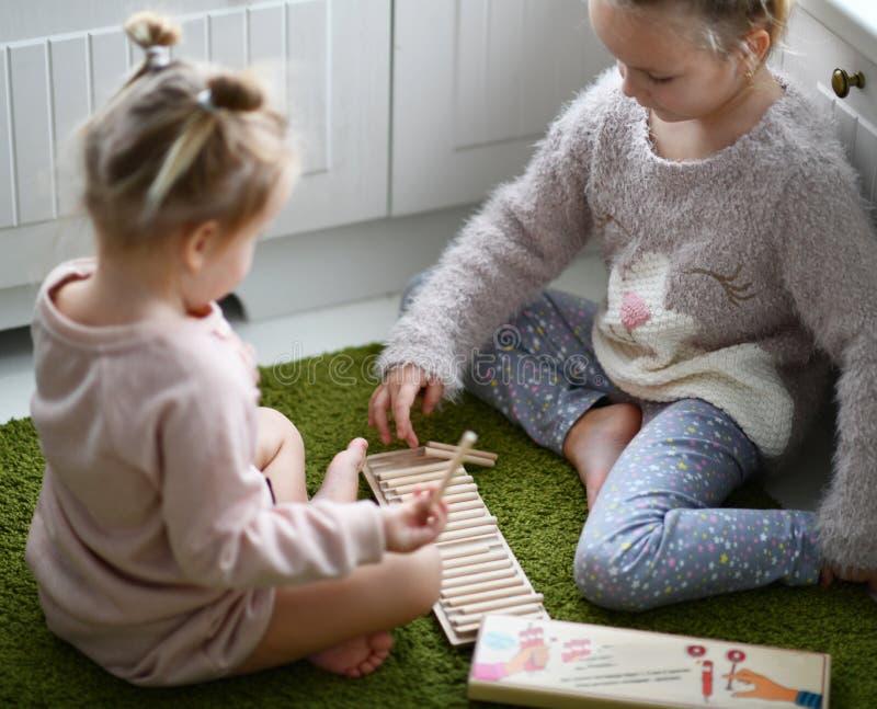 两个孩子女孩在他们的绝尘室打在绿色地毯的教育比赛 免版税库存照片