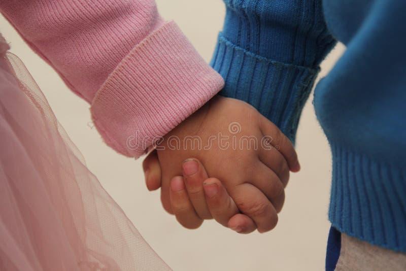 两个孩子手拉手是非常可爱的 库存照片