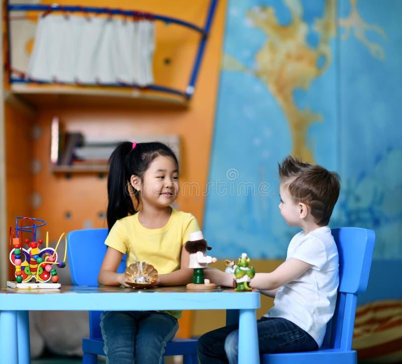 两个孩子男孩和女孩坐在桌上并且演奏玩具医生和闲谈 图库摄影