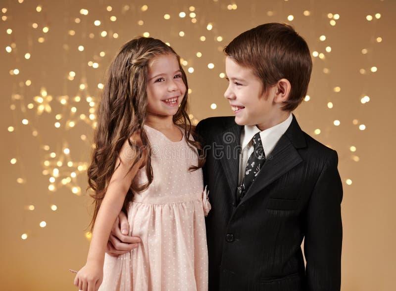 两个孩子男孩和女孩是在圣诞灯,黄色背景,寒假概念 库存照片