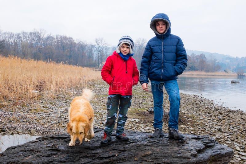 两个孩子画象有狗的在海滩b的一个大岩石 免版税库存照片