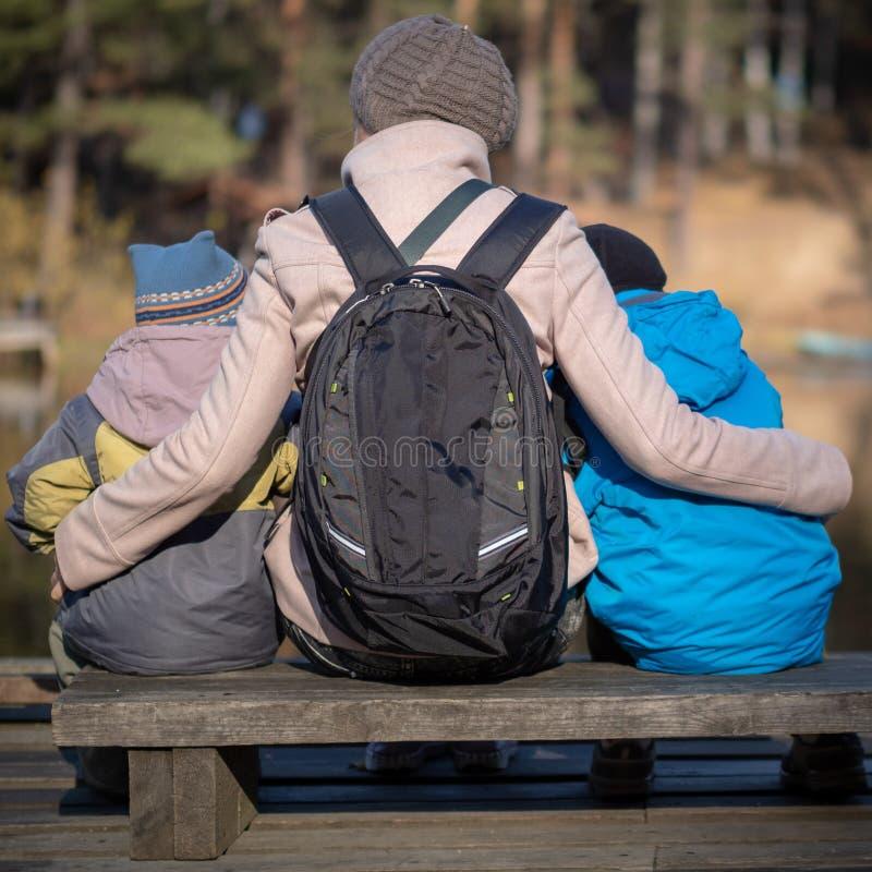 两个孩子的母亲年轻儿子坐公园长椅 免版税库存图片
