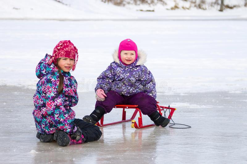两个孩子获得一起坐冰和使用与雪雪撬的乐趣在清楚的冬日 库存图片